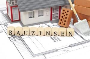 Bauplan mit Ziegelstein und Haus mit Bauzinsen